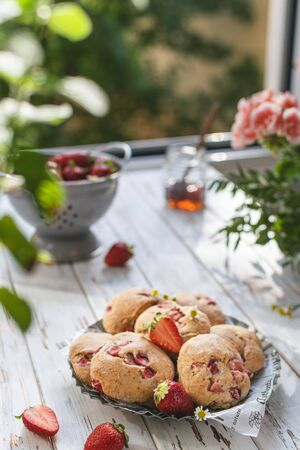Selective focus on strawberry scones, summer breakfast served on rustic wooden background