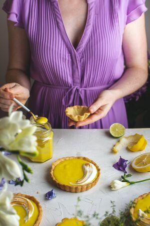 Female hands holding Lemon meringue tart, lemon curd jar, top view, copy space