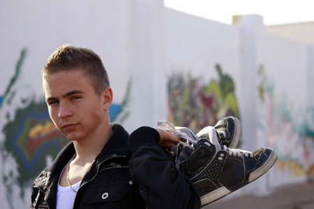 Handsome adolescent with a pair of boots on his hands in front of a graffiti wall photo