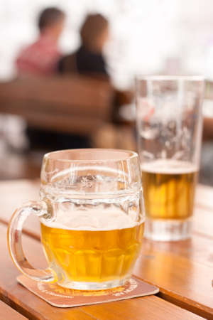 Beer drinking: close-up of a half-filled beer mug on a table in a city restaurant outdoor area photo