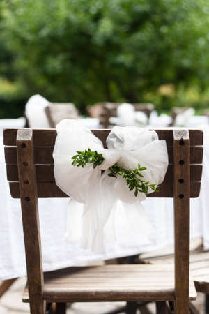 wedding chairs: Detail of countryside wedding decoration: textile chair bow with myrtle branches Stock Photo