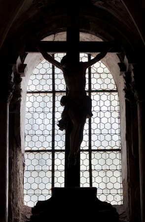 crucified: The silhouette of a wooden statue of Christ on the crosscrucifix in an old baroque chapel (Sedlec ossuary, Czech Republic)