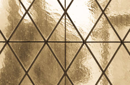 the ancient pass: Old paned translucent glass window background  warm tones  Stock Photo