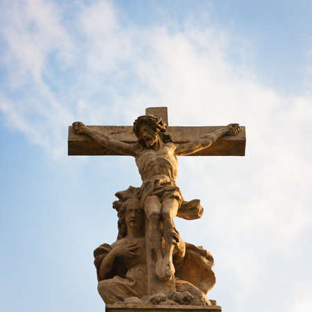 crucified: Statue of Christ with Virgin Mary lying at his feet against blue sky