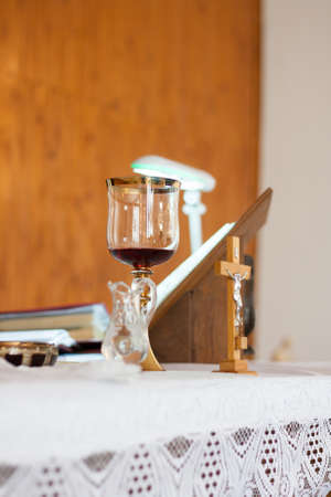 catholic mass: Chalice with the blood of Christ and holy water prepared at the priests desk for a baptism ceremony