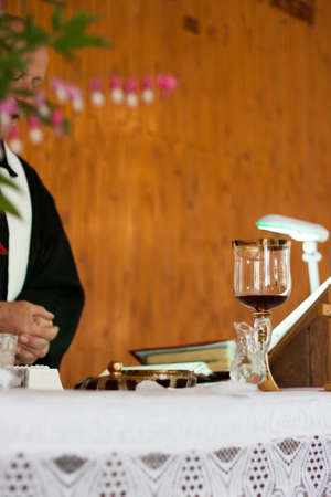 Chalice with the blood of Christ and holy water prepared at the priests desk for a baptism ceremony