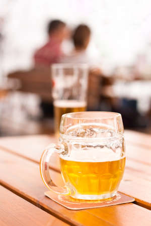bar area: Close-up of a half-filled beer mug on a table in a city restaurant outdoor area Stock Photo