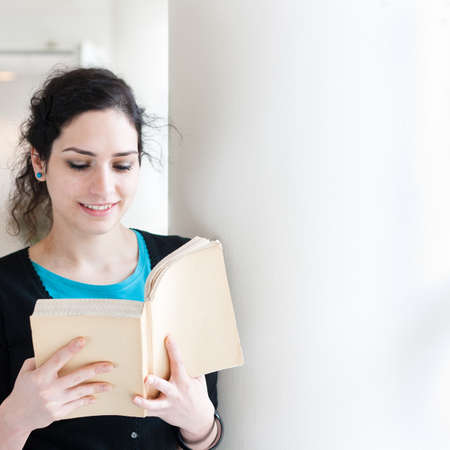 dormitory: Portrait of a young woman reading a book with copy space