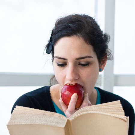 Portrait of a pretty young student eating an apple while reading a book Stock Photo - 12327153
