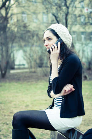 Young woman talking on the phone outdoors in a park photo