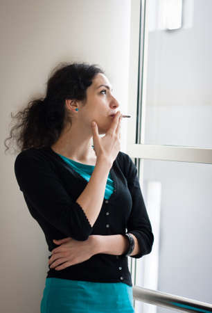 Young woman smoking indoors photo