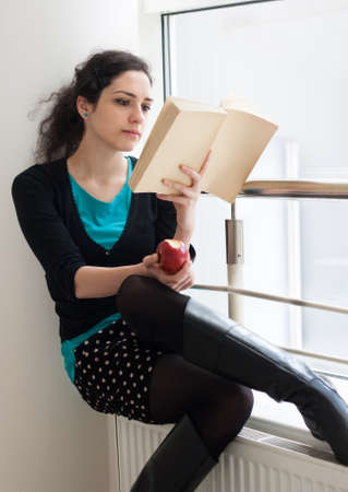 Portrait of a pretty young student eating an apple while reading a book