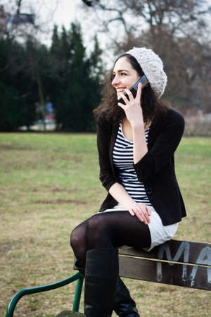 sitting on a bench: Young woman talking on the phone outdoors in a park Stock Photo