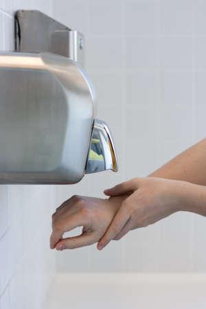 salud publica: Secarse las manos en un ba�o p�blico (atenci�n selectiva) Foto de archivo