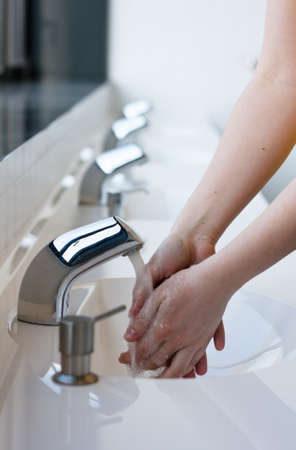 Washing hands in a public restroom (selective focus) Stock Photo - 12715004