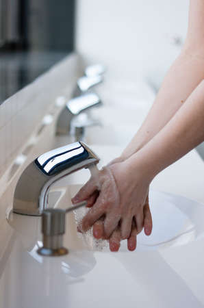 Washing hands in a public restroom (selective focus) photo