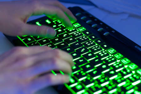 Closeup of hands typing a modern backlit keyboard photo