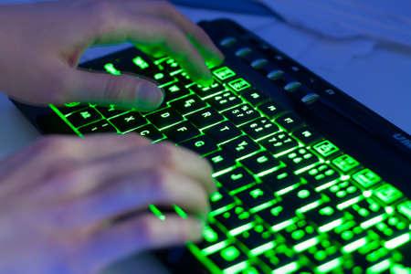 backlit keyboard: Closeup of hands typing a modern backlit keyboard Stock Photo