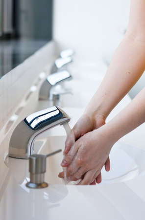 Washing hands in a public restroom  selective focus  photo