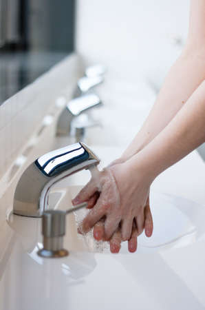Washing hands in a public restroom  focus on the tap, hands in motion  Stock Photo
