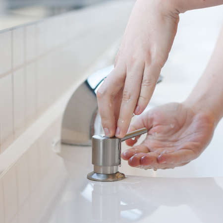 Washing hands in a public restroom - applying soap  selective focus  photo
