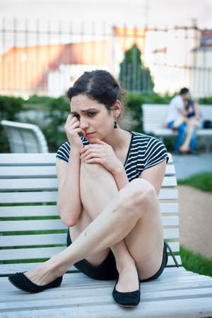 heartsick: Depressed young woman sitting on a bench in an urban area