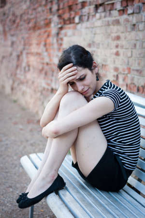 heartbroken: Depressed young woman sitting on a bench in an urban area