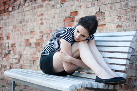 Depressed young woman sitting on a bench in an urban area photo