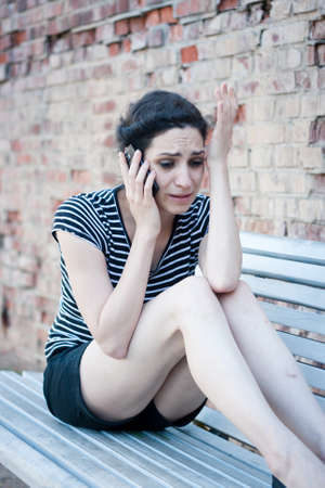 sitting area: Unhappy young woman crying while talking on the phone