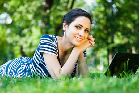 Beautiful young woman  using her laptop outdoors in a park at campus photo