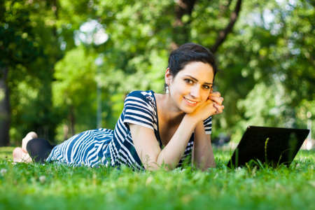 Beautiful young woman  using her laptop outdoors in a park at campus