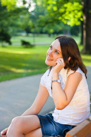 Pretty young businesswoman talking on the phone outdoors in a city park Stock Photo