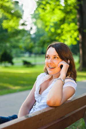 Pretty young businesswoman talking on the phone outdoors in a city park photo