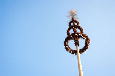 maypole: Maypole decorated with garlands against blue sky