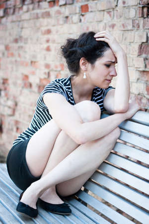 Depressed young woman sitting on a bench in an urban area Stock Photo - 14430828