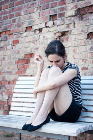 joven fumando: Mujer deprimida joven fumando un cigarrillo al aire libre en una zona urbana