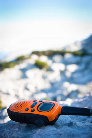 Closeup of a walkie-talkie laid aside on a rock while the hiking expedition is having a rest