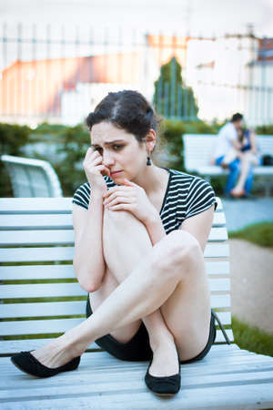 sitting area: Depressed young woman sitting on a bench in an urban area