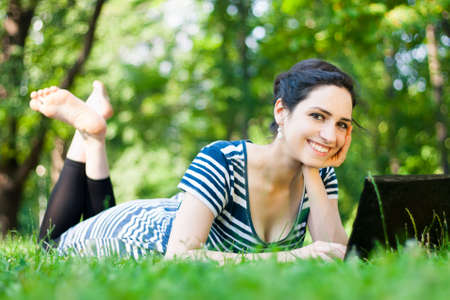 Beautiful young woman  using her laptop outdoors in a park/at campus photo