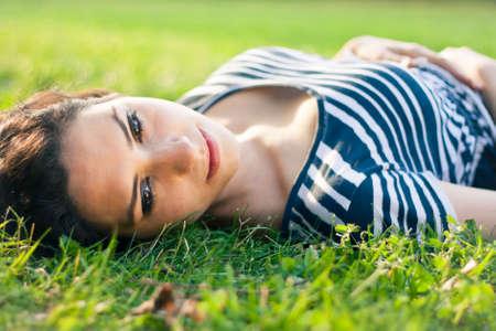 Closeup of a beautiful young woman lying in grass