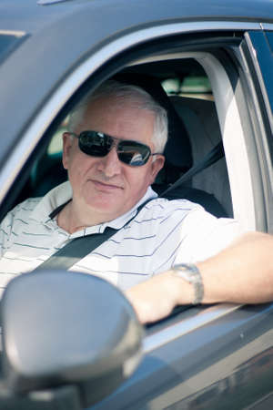 Handsome middle-aged man driving a modern car photo
