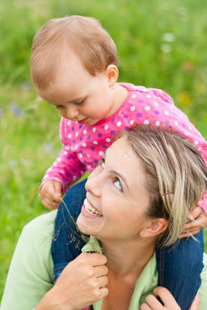 Young mother and her baby girl playing while outdoors on a walk Stock Photo