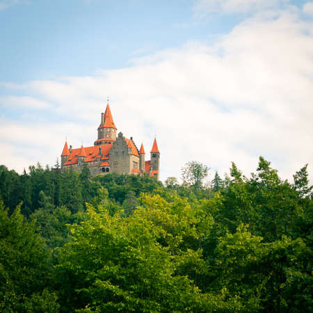 The romantic castle of Bouzov emerging from the forest against blue sky