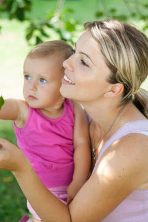 Young mother playing with her baby girl outdoors in the garden photo