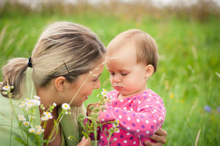 Young mother and her baby girl playing while outdoors on a walk photo