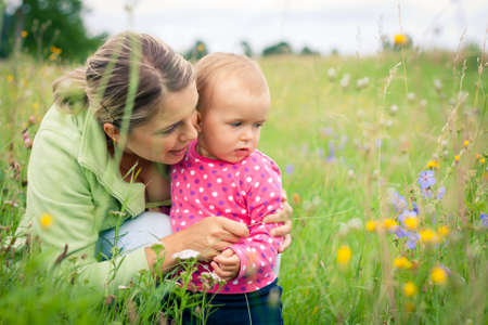 Young mother and her baby girl playing while outdoors on a walk Stock Photo - 14943087