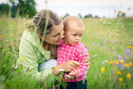 Young mother and her baby girl playing while outdoors on a walk Stock Photo - 14943084