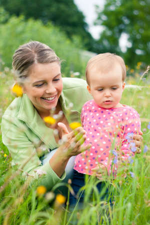 Young mother and her baby girl playing while outdoors on a walk Stock Photo - 14943072