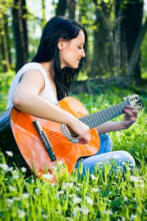 music therapy: Mujer joven que toca la guitarra al aire libre