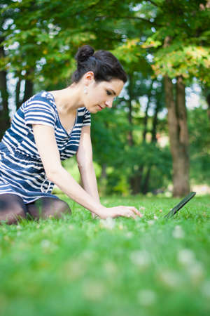 College student using her laptop outdoors at campus photo